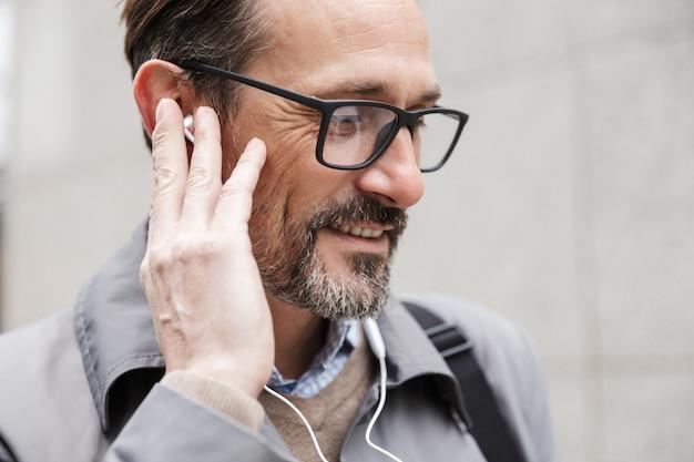 Zbliżenie obrazu zadowolonego biznesmena w okularach za pomocą słuchawek, stojąc w pobliżu biurowca