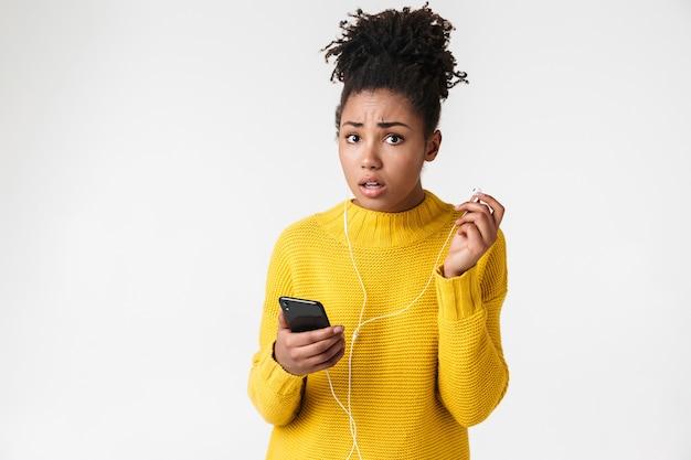 Zbliżenie obrazu zaintrygowanej kobiety afroamerykanów, trzymając telefon komórkowy i słuchanie muzyki przez słuchawki na białym