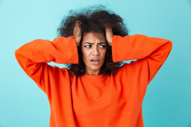 Zbliżenie obrazu zdezorientowanej kobiety w czerwonej koszuli, patrząc na bok i chwytając głowę z kudłatymi włosami, odizolowane na niebieskiej ścianie