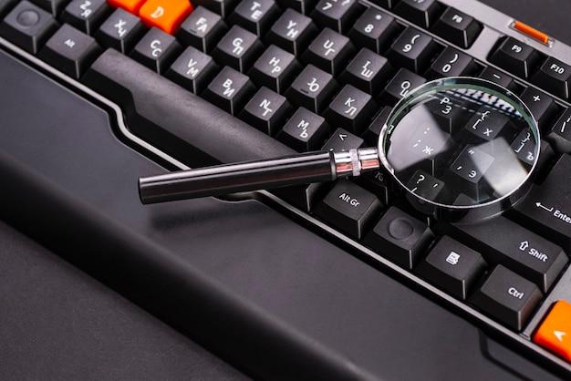 Zbliżenie obrazy szkła powiększającego na klawiaturze laptopa.