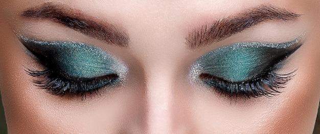 Zbliżenie oczu młodej dziewczyny z pięknym makijażem