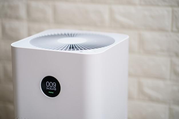 Zbliżenie oczyszczacza powietrza z ekranem monitora, pokazuje jakość powietrza w pokoju. koncepcja pm2,5.