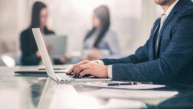Zbliżenie - odnoszący sukcesy biznesmen pracujący na laptopie z danymi finansowymi w miejscu pracy w nowoczesnym biurze. zdjęcie ma puste miejsce na tekst