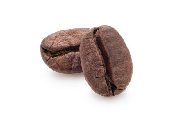 Zbliżenie odosobnione świeże dwa pieczonej kawowej fasoli lub ziarna na białym tle. zdjęcie ścieżki przycinającej.