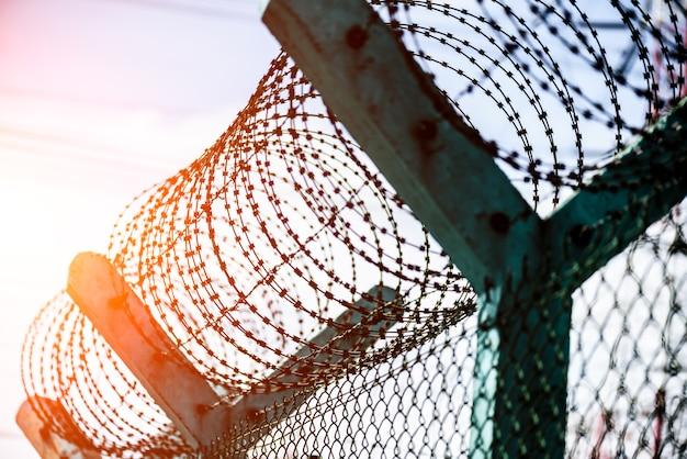 Zbliżenie ogrodzenie zabezpieczające z drutem kolczastym. prawa człowieka i abstrakcja społeczna sprawiedliwości.