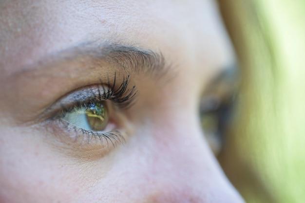Zbliżenie oko kaukaski brunetka kobieta. portret młodej kobiety. kaukaski tło twarzy dziewczyny, z bliska oczy