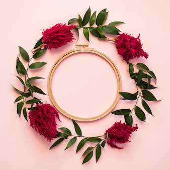Zbliżenie okrąg świezi kwiaty i zieleni liście kłama na różowym tle - odbitkowa przestrzeń