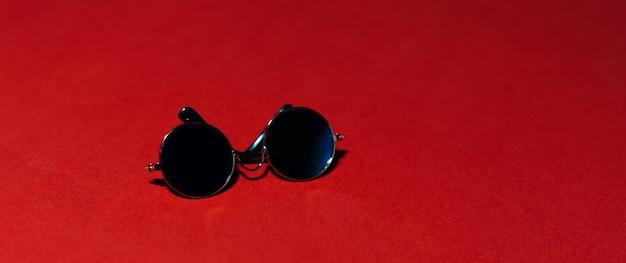 Zbliżenie okrągłe okulary na czerwonym tle. panoramiczny widok na baner.
