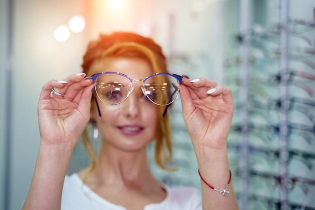 Zbliżenie okularów. okulary w rękach kobiety. prezentowanie okularów. zbliżenie