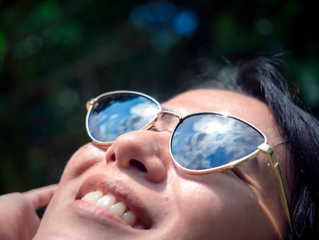 Zbliżenie okularów przeciwsłonecznych z odbiciem błękitnego nieba na twarzy pięknej kobiety, patrząc w górę