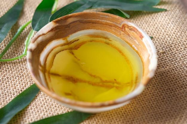 Zbliżenie oliwy z oliwek w pojemniku i liść na stole