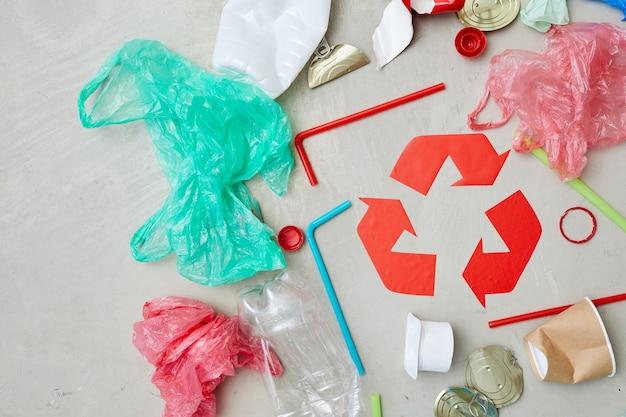 Zbliżenie opakowań wokół czerwonego symbolu recyklingu na białym tle na szarym tle