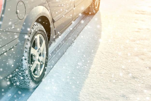 Zbliżenie: opony gumowe koła samochodu w głębokim śniegu zimą. koncepcja transportu i bezpieczeństwa.
