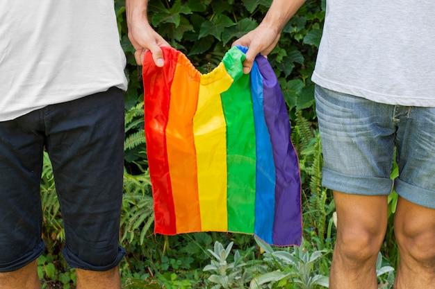 Zbliżenie osób posiadających flagę dumy gejowskiej