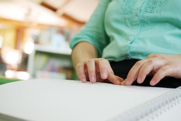 Zbliżenie: osoba niewidoma ręce kobiety, czytanie książki braille'a studiowanie w kreatywnej bibliotece.