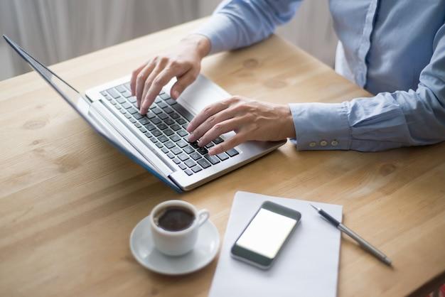 Zbliżenie osoba pracuje na laptopie w kawiarni