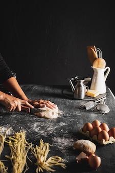 Zbliżenie osoby cięcia ciasta za pomocą przyborów kuchennych