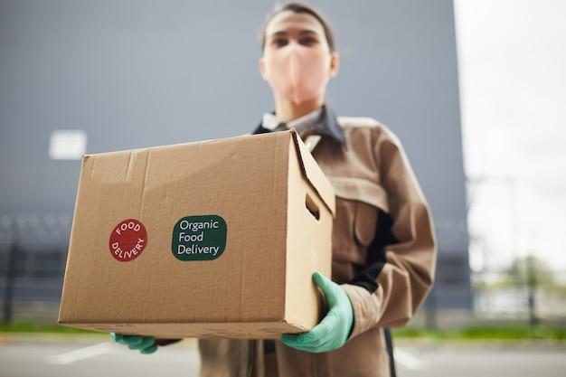 Zbliżenie osoby dostawy posiadającej duży karton na zewnątrz, ona dostarcza jedzenie