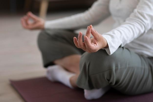 Zbliżenie osoby medytującej w domu