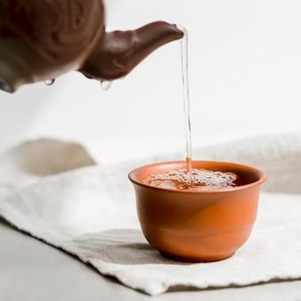 Zbliżenie osoby wlewając filiżankę herbaty z czajnikiem