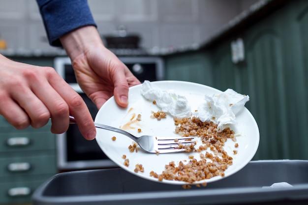 Zbliżenie osoby wyrzucającej z talerza resztki gryki do kosza na śmieci. skrobanie odpadów żywnościowych
