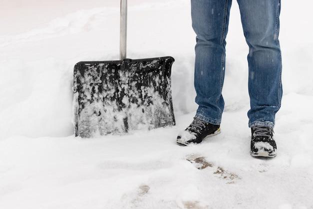 Zbliżenie osoby z łopatą do śniegu na podjeździe usuwanie śniegu po zamieci śnieżnej