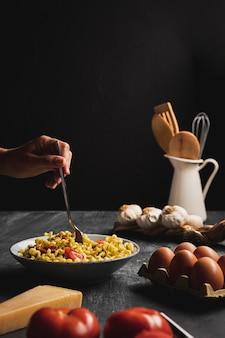 Zbliżenie osoby z makaronem i jajkami