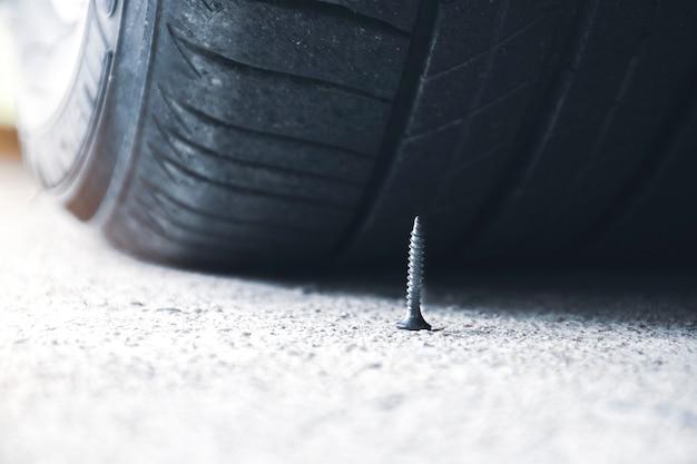 Zbliżenie ostrej metalowej śruby na drodze prawie do przebicia opony samochodowej
