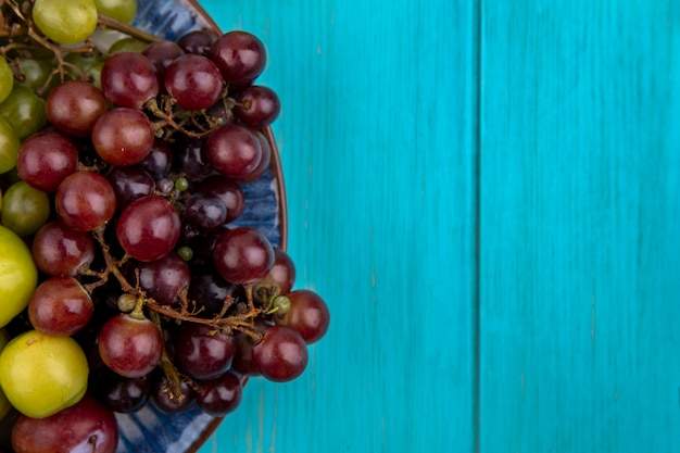 Zbliżenie owoców jak śliwki i winogrona w płycie na niebieskim tle z miejsca na kopię