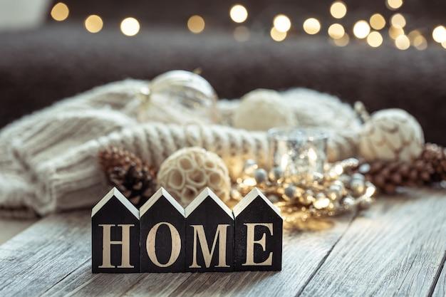 Zbliżenie: ozdobne słowo do domu, szczegóły świątecznego wystroju na niewyraźne tło z bokeh.