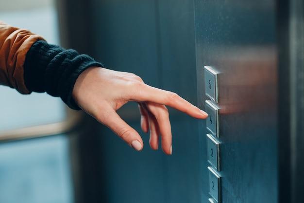 Zbliżenie palca wskazującego naciskającego przycisk windy podczas pandemii koronawirusa covid-19 koncepcji kwarantanny