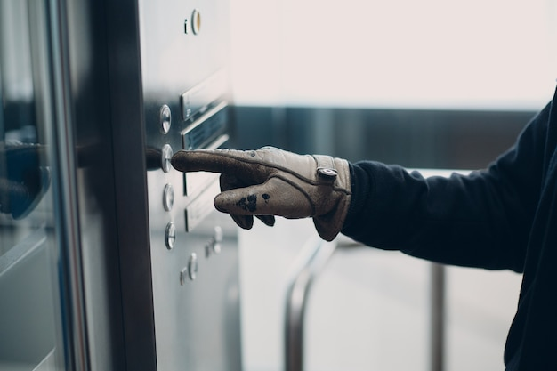Zbliżenie palca wskazującego w rękawiczce, naciskając przycisk windy podczas koncepcji kwarantanny pandemii koronawirusa covid-19