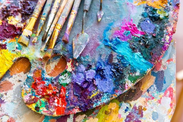 Zbliżenie palety artystycznej z jasnymi kolorowymi farbami mieszanymi, pędzlem i nożami do palet