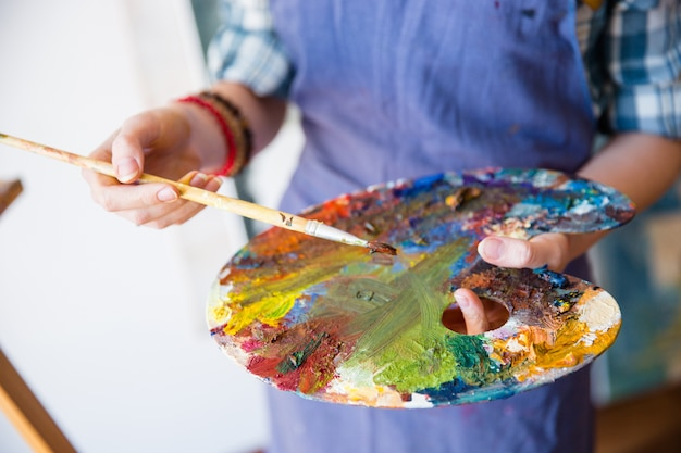 Zbliżenie palety z mieszanymi farbami trzymanymi przez młodą artystkę