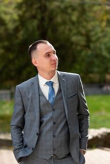 Zbliżenie pan młody w szarym garniturze z niebieskim krawatem mężczyzna odwraca wzrok i przygotowuje się do ślubu