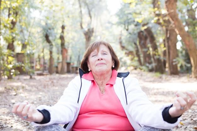 Zbliżenie pani medytuje na zewnątrz
