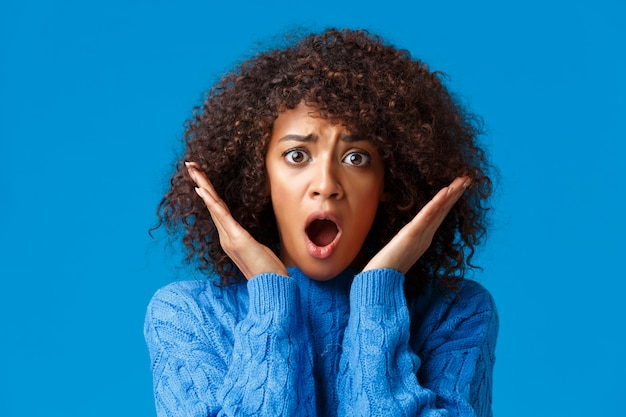 Zbliżenie panikuje, zmartwiona i zszokowana afroamerykańska kobieta z kręconymi fryzurami afro, z trudem łapiąc powietrze, podnosi ręce w pobliżu twarzy, wpatruje się w straszną złą scenę, stoi przerażona na niebiesko
