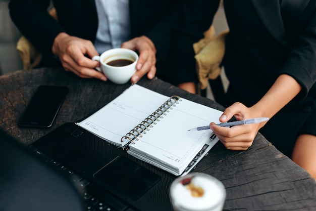 Zbliżenie papierowego terminarza. ręka trzyma długopis i wskazuje na arkusz.