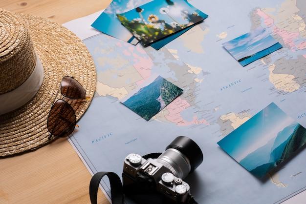 Zbliżenie papierowej mapy ze zdjęciami natury, okularami przeciwsłonecznymi, aparatem i słomkowym kapeluszem