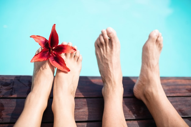 Zbliżenie: para bosych stóp przeciwko basen w słoneczny dzień