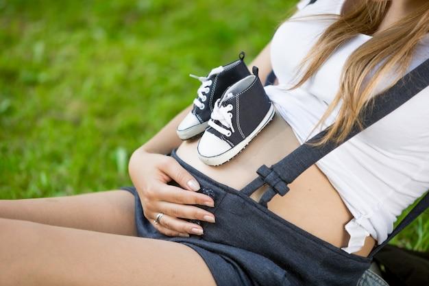 Zbliżenie para butów dziecięcych na brzuchu kobiety w ciąży leżącej na trawie