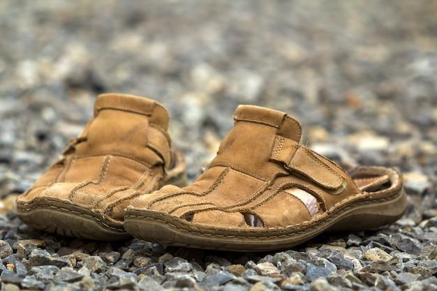 Zbliżenie: para starych noszonych wygodnego mężczyzny klasyczne skórzane miękkie brązowe letnie buty sandały na zewnątrz kamienne otoczaki sceny. nowoczesna odzież dla mężczyzn w codziennym życiu, styl i wygoda.