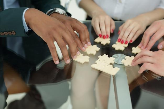 Zbliżenie.partnerzy biznesowi rozliczający elementy układanki.koncepcja współpracy