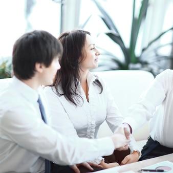 Zbliżenie. partnerzy finansowi ściskają ręce nad biurkiem w biurze