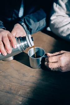 Zbliżenie pary starszych rąk nalewanie kawy do metalowego kubka z termosu na drewnianym stole