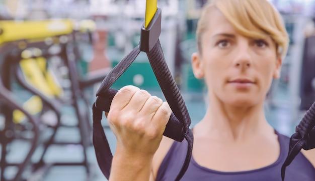 Zbliżenie pasek fitness w ręce kobiety robi twarde zawieszenie szkolenia w centrum fitness. koncepcja zdrowego i sportowego stylu życia.