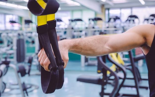 Zbliżenie pasków fitness w ręku człowieka robi twarde zawieszenie szkolenia w centrum fitness. koncepcja zdrowego i sportowego stylu życia.