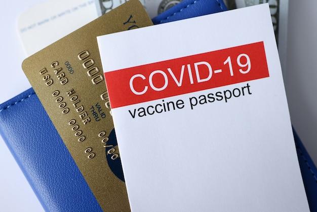 Zbliżenie paszportu szczepień covid 19 i karty kredytowej. podróżowanie w okresie pandemii covid19