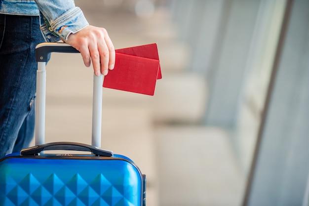Zbliżenie paszporty i karta pokładowa przy lotniskowym salowym tło samolotem