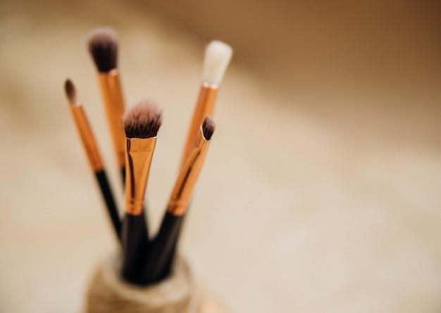 Zbliżenie pędzle do makijażu. niewyraźne beżowe tło wykonane z papieru kraft. obraz monochromatyczny.